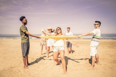 armonia: Grupo de amigos felices y juguetones que juegan en el limbo en la playa - Los turistas de vacaciones en un destino turístico tropical en el verano Foto de archivo