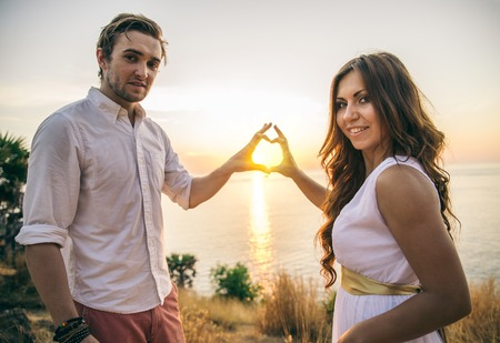 wedding heart: Couple in love kissing at sunset - Lovers on a romantic date outdoors making a heart shape with hands Stock Photo