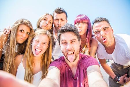 カメラ - パーティーで楽しんで、自分自身を撮影しながら変な顔を作って幸せな若者の前で顔をゆがめた友人のグループ