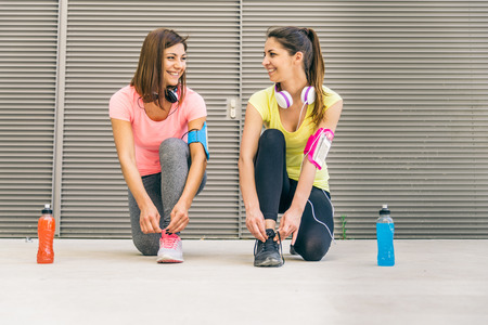 keep fit: Team of urban runners getting ready for training - Sportive women with sportwear tying shoelaces  - Friends working out to keep fit and healthy