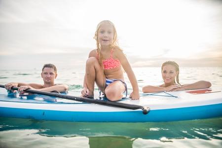 Счастливая семья с веслом борту купания в океане - Довольно молодая девушка улыбается в то время как обучение грести - Портрет активного и спортивного семьи на отдых на летнее