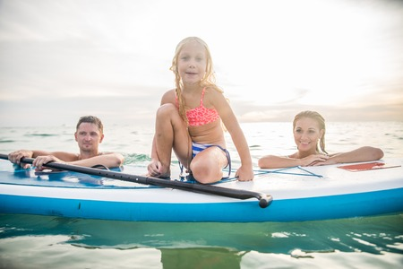 hawaii beach: Happy family with paddle board swimming in the ocean - Pretty young girl smiling while learning to paddle - Portrait of active and sportive family on vacation on summertime