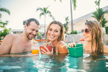 Friends having party and drinking buckets at a swimming pool party - Tourists on vacation in a beautiful tropical resort during summertime Stock Photo
