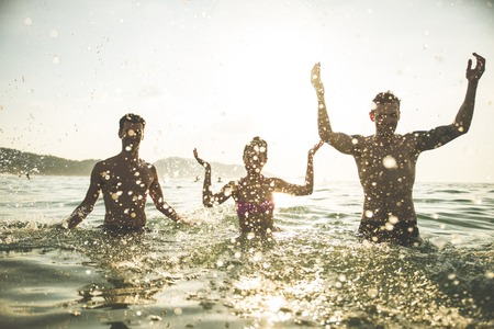 Group of happy friends jumping in to water at sunset - Silhouettes of active people dancing and having fun on the beach on vacation
