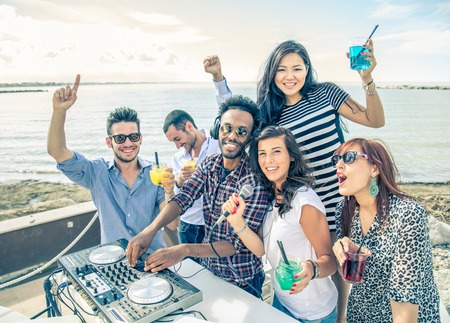 Dj playing trendy music in a open air club - People dancing and partying while the disc jockey mixes two song tracks at at summer concert