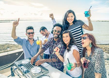 gente bailando: DJ que juega música de moda en un club al aire libre - Gente bailando y fiesta mientras que el disc jockey mezcla dos pistas de la canción en al concierto de verano Foto de archivo