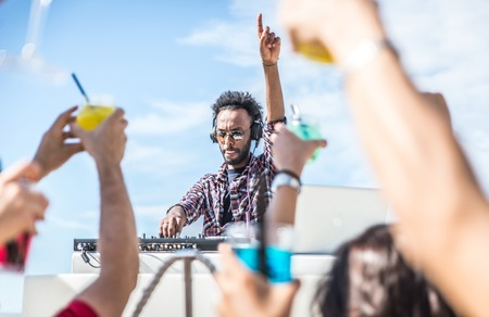 fiesta: dj set en la fiesta en la playa. DJ hace girar la música y la gente está muy entusiasmado con las manos arriba. concepto sobre la fiesta, la música y la gente