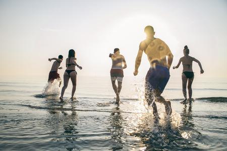 석양에 물에 실행하는 행복 친구의 그룹 - 휴가 해변에서 재미 활동적인 사람의 실루엣 - 관광객 열대 섬 수영 것