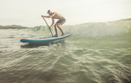 to stand: surfer with paddle board catching the wave. concept about sport and people