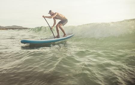 ocean kayak: surfista con tabla de paddle agarrar la ola. concepto sobre el deporte y la gente
