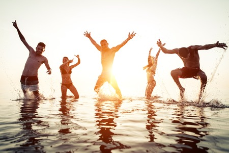 ibiza: group of friends having fun in the water at the sunrise. concept about vacations, sea places, friendship and people