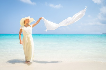 long: Beautiful woman with long white dress and hat walking on a tropical beach with crystalline water - Fashion model in a idyllic vacation resort