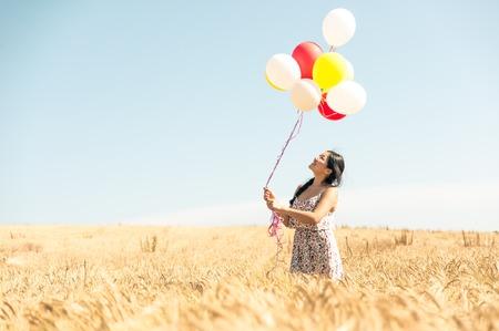 schöne asiatische Frau in einem Weizenfeld mit Luftballons. Konzept über Leichtigkeit und unbeschwerten