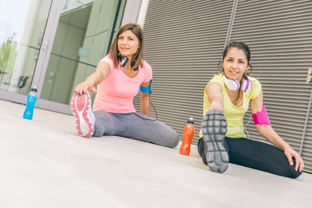 muscled: Team of urban runners getting ready for training - Sportive women with sportwear stretching before running  - Friends working out to keep fit and healthy Stock Photo