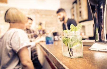 バーでカクテルをクローズ アップ。バーテンダーとお客様は後ろに立っています。についての概念バー、専門職および人々。