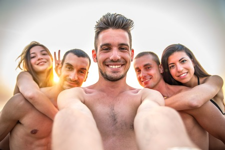 women having fun: Multiethnic group of friends enjoying vacation  and taking a picture withcamera - Mixed group of several people having fun on the beach at sunset Stock Photo