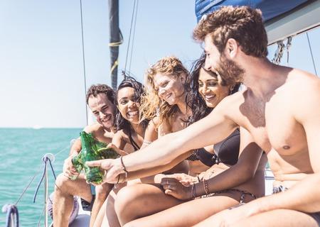 niñas bonitas: Grupo de amigos que hacen la tostada en el barco. El tostar con las botellas de cerveza durante una excursión