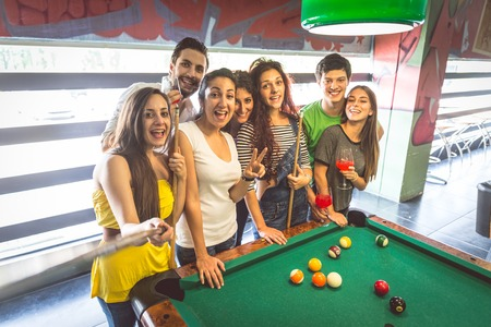 billiard: Group of multiracial young people standing next to pool table and taking a selfie - Students spending an evening at pub Stock Photo