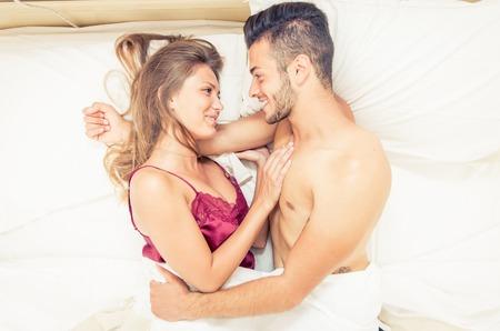 enamorados en la cama: Pareja feliz despertar en el amor. Abrazos y sonrisas entre s� Foto de archivo