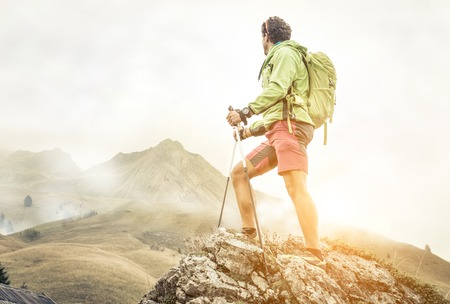 hiker climbing on the mountains. he stays on the top of a rock and watch his goal.