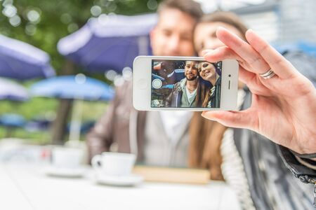 self   portrait: Couple sitting at restaurant table taking a self portrait with phone - Friends in a bar looking at cell phone Stock Photo