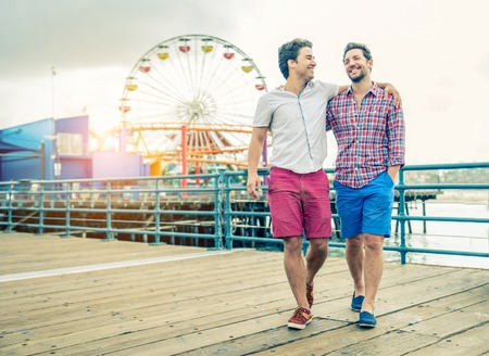 Homosexual couple walking on a pier at sunset - Two lovers hugging and having a walk outdoors Stock Photo