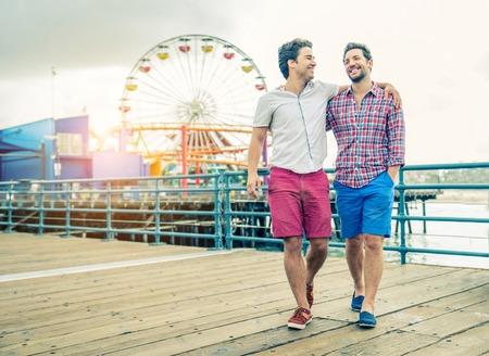 sexo: pareja homosexual caminando sobre un muelle en la puesta del sol - Dos amantes que abrazan y que tiene una caminata al aire libre
