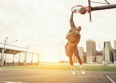 Rua jogador de basquete realizando poder favela enterrada. Manhattan e New York City no fundo Banco de Imagens