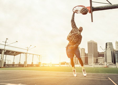 outdoor basketball court: Street basketball player performing power slum dunk. Manhattan and New york city in the background
