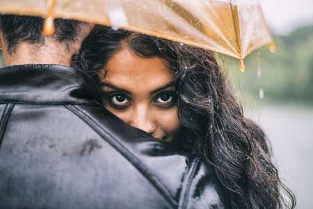 Multiethnic couple of lovers hugging under the umbrella on a rainy day -  Man and woman on a romantic date under the rain, boyfriend hugs his partner to protect her