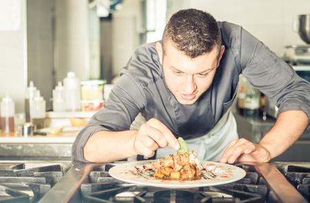 Giovane cuoco unico che prepara un pasto gustoso. Concetto su ristoranti e prodotti alimentari