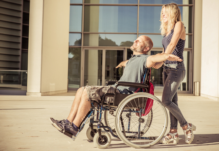 Woman and his boyfriend on the wheelchair going out. concept about deseases and people