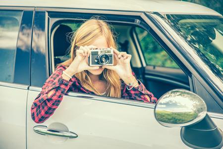 mujer alegre: Mujer bonita joven que fotografía con la cámara, mientras que en una excursión en la naturaleza Foto de archivo