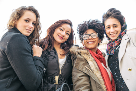 Group of attractive young women of different ethnies sitting on stairs and smiling at camera - Four students sitting outside university - Best friends spending time together Фото со стока