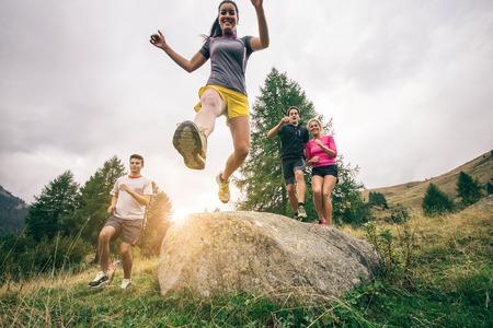 utbildning: Löpare utbildning på en off road spår - Gruppen vandrare promenader i naturen vid solnedgången - Vänner tar en excursionon ett berg Stockfoto