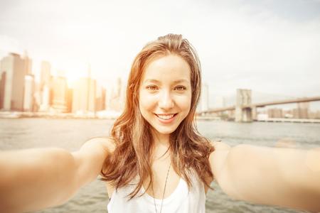 Menina asiática bonita que prende a câmera e tendo auto-retrato em Nova York. Ponte de Brooklyn e skyline de New York em segundo plano