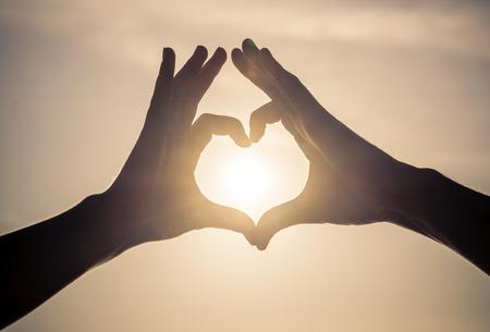 空にカップルの作る愛のシンボル。ハート図を作る 2 つの腕のシルエット。 写真素材