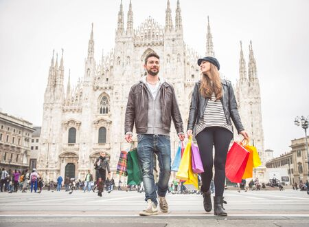 Couple buying presents during a sale - Attractive man and woman holding shopping bags and having fun - Autumn and winter mood photo