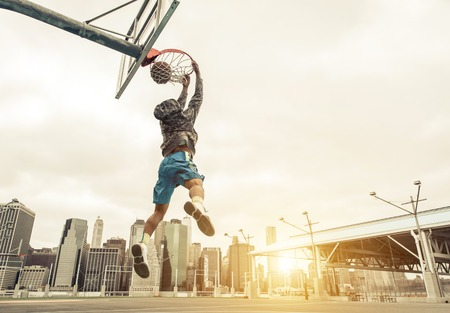 outdoor basketball court: Basketball street player making a rear slam dunk. New york and Manhattan buildings in the background