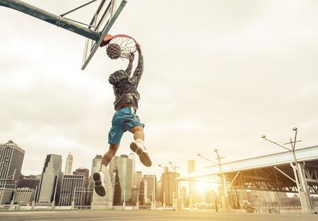 juventud: Jugador de básquet de la calle haciendo un slam dunk trasera. Nueva York y Manhattan edificios en el fondo Foto de archivo