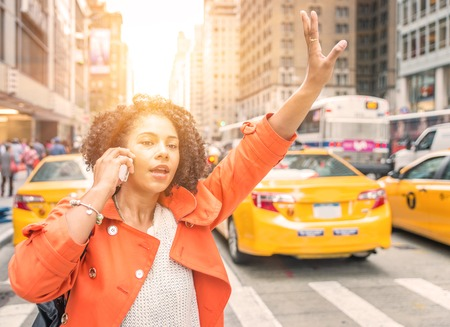 afro american woman calling a taxi in New York near Time square district. concept about urban life, people and transportation