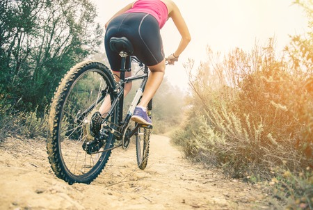 off road biking: Woman riding her mountain bike on a off road track - Athletic girl cycling in the nature at sunset, close up on tire and lower body