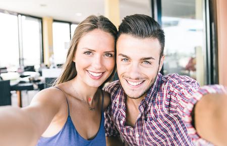 femmes souriantes: Couple de prendre autoportrait avec un téléphone intelligent. Belle jeune couple selfie Banque d'images