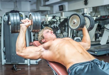 bodybuilder: Culturista joven entrenando duro. Pectoral trabajar con pesas Foto de archivo