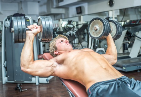 muscle building: Young bodybuilder training hard. Pectoral work out with weights Stock Photo