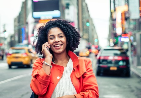 yellow cab: american woman making a phone call in Time Square, New york. urban lifestyle concept