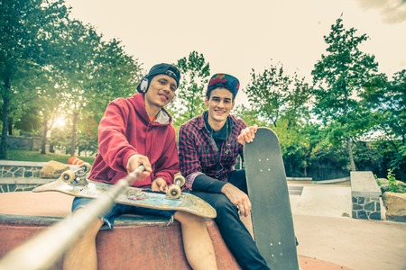 holding: Two young men in a skate park holding a selfie stick and photographing themselves - Two skaters having fun on a skate competition