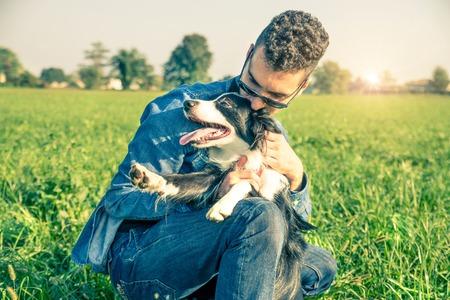 hombres jovenes: Hombre joven acariciando su perro juguetón - Cool perro y hombre joven que se divierte en un parque - conceptos de amistad, animales domésticos, unidad