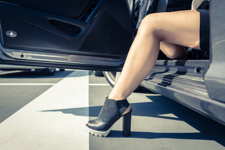 donna ricca: Donna di uscire dalla macchina. Primo piano sulla porta della cabina e la gamba ragazza Archivio Fotografico