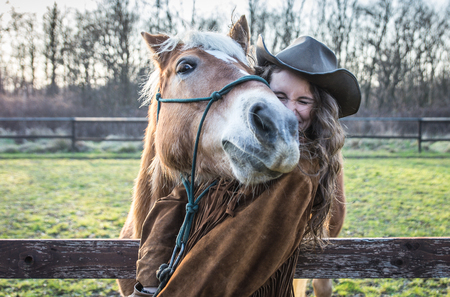 droll: Funny portrait of a girl with an horse. Playing together at the farm. concept about people and animals